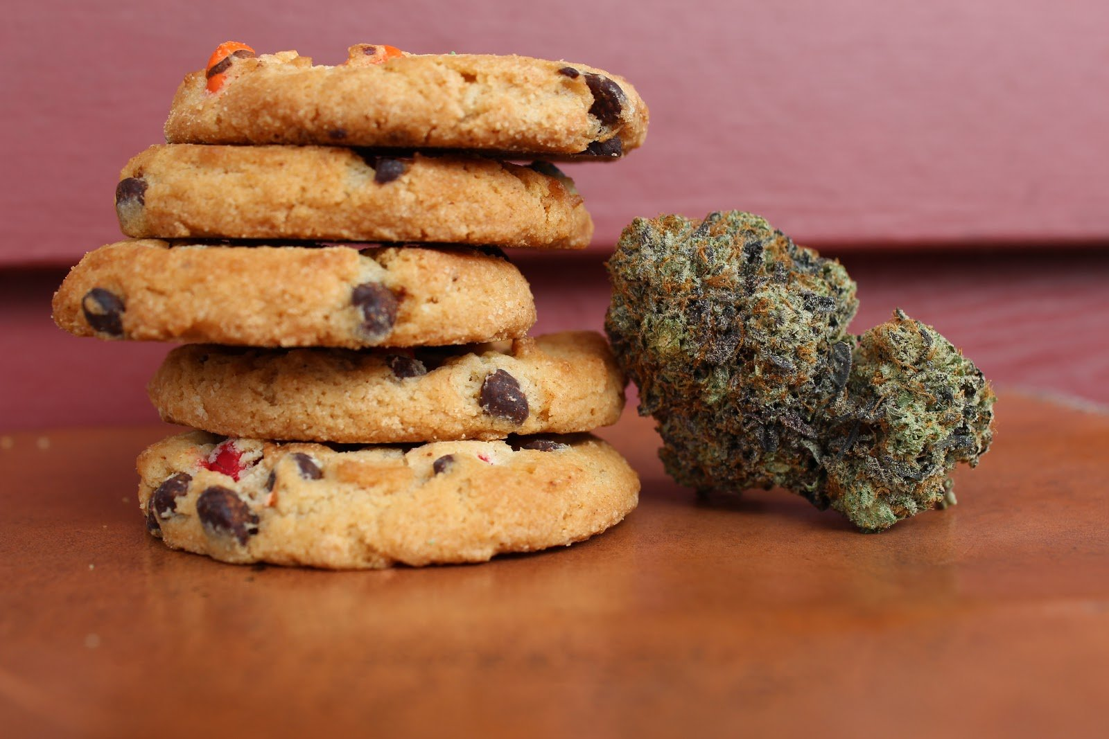 chocolate chip cookies are stacked next to a gram of cannabis